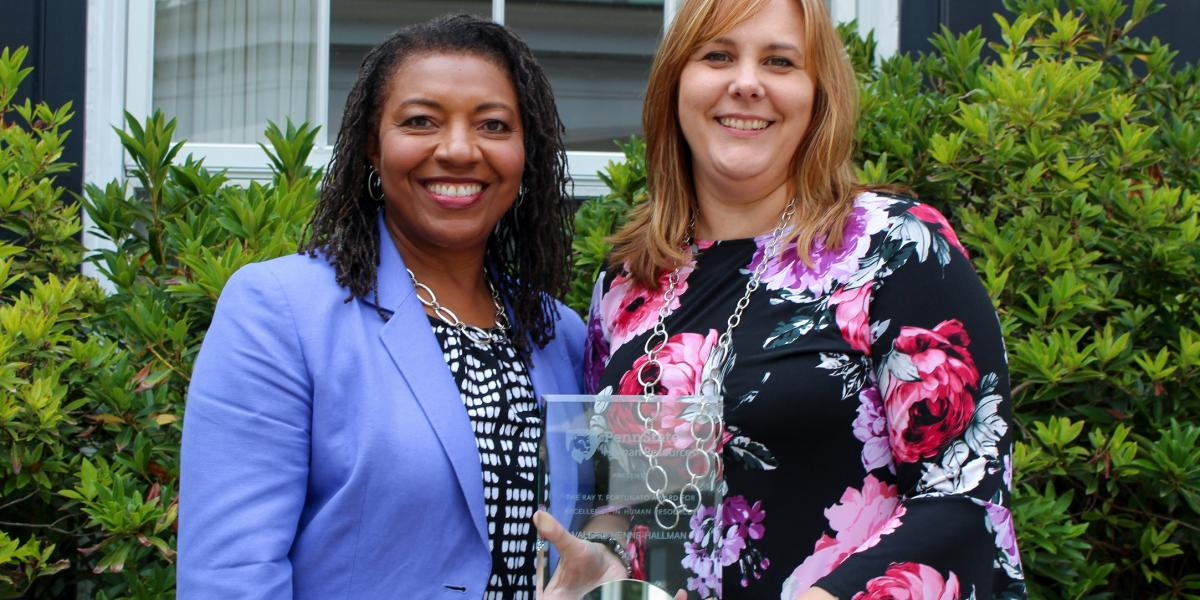 Lorraine Goff and Valerie Henne-Hallman standing together with the award.